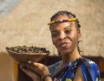 Nación bantú sonriente de la mujer joven que sirve las orugas comestibles para la cena Viñedo famoso de Kanonkop cerca de las mon fotografía de archivo libre de regalías