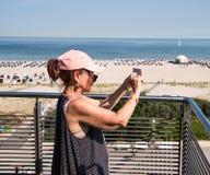 Nacido en el baby boom de la mujer que lleva la gorra de béisbol rosada en la terraza que toma el pi fotos de archivo libres de regalías