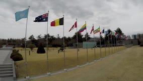Naciones Unidas y bandera nacional que agitan en el aire del cementerio conmemorativo de la O.N.U en Busán, Corea del Sur, Asia almacen de metraje de vídeo