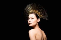Nackte Dame in der goldenen Kopfbedeckung, die weg auf Schwarzem lokalisiert schaut Stockbild