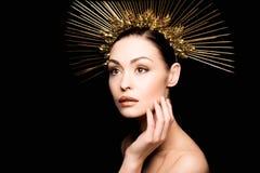 Nackte in der goldenen Kopfbedeckung, die ihr Gesicht berührt Lizenzfreie Stockfotos