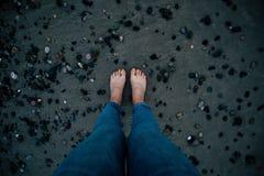 Nackte Füße der Frau mit Blue Jeans auf schwarzem Sand und Draufsicht der Steine lizenzfreie stockfotos