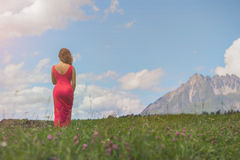 Nackte Frau in einem roten Kleid auf einem Gebiet bei Sonnenuntergang Lizenzfreie Stockbilder
