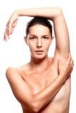 Nackte Frau im Studio mit dem Arm obenliegend Stockfotografie