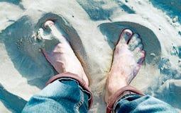 Nackte männliche Beine im Strandsand stockfotos