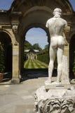 Nackte männliche Statue von hinten mit Ansicht durch Bogen und des gestreiften Grases Stockfoto