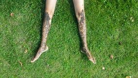 Nackte schmutzige Beine auf dem Gras Lizenzfreie Stockfotos