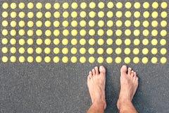Nackter Mensch barfuß auf Asphaltstraße an Taststöße pavin Stockfotografie
