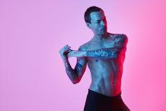Nackter Torso des muskulösen Sportmannes, der Arm herstellt auszudehnen auf einem Farbhintergrund Studiomodeporträt des sexy spor stockfotografie