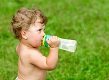 Nacktes Baby, das auf einer Flasche Wasser gegen saugt Stockfotografie