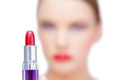 Nacktes blondes Modell, das roten Lippenstift hält Stockfoto