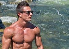 Nacktes Freien des attraktiven jungen Muskelmannes mit Wasser hinter ihm Stockbild