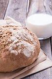 Naco de pão com leite em uma tabela velha da prancha Fotografia de Stock
