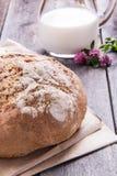 Naco de pão com leite em uma tabela velha da prancha Imagens de Stock Royalty Free