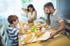Naco do corte da mulher de pão quando família que come o café da manhã Foto de Stock Royalty Free