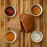 Naco tradicional do pão escuro de Flatlay em uma placa com fatias, com foto de stock