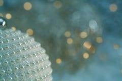 Nacre σφαιρών Χριστουγέννων μαργαριτάρια και όμορφο θολωμένο μπλε υπόβαθρο της ακτινοβολίας bokeh με τα φω'τα πυράκτωσης Παιχνίδι στοκ φωτογραφίες με δικαίωμα ελεύθερης χρήσης