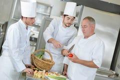 Naczelny szef kuchni pracuje z asystentami zdjęcie stock