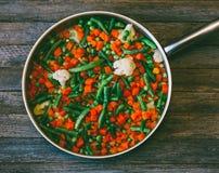 Naczynie azjata kuchnia jarzynowa mikstura marchewki, grochy, fasolki szparagowe i kalafior w smaży niecce, Obrazy Stock
