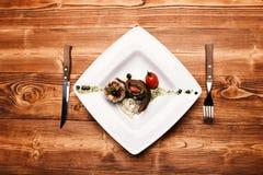 Naczynie z nowożytną prezentacją na kwadrata talerzu Piec wieprzowina stek obraz royalty free