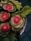 Naczynie z ogórkami i pomidorami, sałatkowy liść na stole na zielonym tle, zdjęcia royalty free