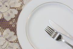 Naczynie z rozwidleniem i nóż z koronkowym tablecloth tłem Zdjęcia Royalty Free