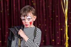 Nadąsana chłopiec jest ubranym twarzy farbę na scenie Zdjęcie Royalty Free