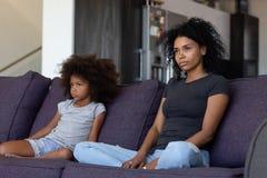 Nadąsany afrykański dziecka i matki obsiadanie na kanapie no opowiada obraz royalty free