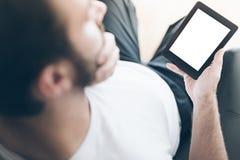 Nad naramiennym widokiem mężczyzna obsiadanie na karle używać ebook czytelnika lub pastylka komputeru obraz royalty free