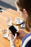 Nad naramiennym widokiem młoda kobieta pisać na maszynie na telefonie komórkowym Fotografia Royalty Free