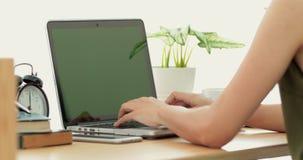 Nad ramię strzałem Azjatycka kobieta pisać na maszynie na laptopie z kluczowym zieleń ekranem zbiory