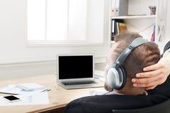 Nad ramię strzałem biznesmen w biurze słucha muzykę w hełmofonach zdjęcie stock