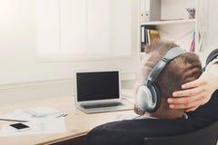 Nad ramię strzałem biznesmen w biurze słucha muzykę w hełmofonach fotografia royalty free