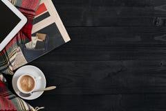 Nad widok gazeta, szalik w klatce, pastylka i filiżanka latte kawa na czarnym drewnianym tle, Zdjęcie Royalty Free