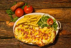 Nad widok wyśmienicie pizzy i francuza dłoniaki, pomidor, marchewka na drewnianym stole przygotowywającym jeść w domu fotografia royalty free
