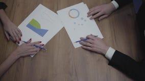 Nad widoku strzał graficznych dane szablonów stół z unrecognizable ludzie biznesu analizuje stopień wzrostu i trendy zdjęcie wideo