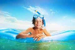 Nadada caucásica agradable sonriente del muchacho en matrass Foto de archivo libre de regalías