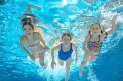 A nadada da família na associação ou o mar subaquática, a mãe e as crianças têm o divertimento na água Imagens de Stock Royalty Free