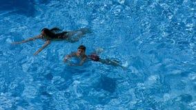 Nadada de dos niños en piscina junto almacen de metraje de vídeo