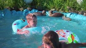 Nadada de dos pequeña niños en una pequeña charca Brother y hermana que ríen, salpicando el agua Nadada de los niños en un día de almacen de video