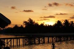 Nadada de la puesta del sol de la playa de la isla de Maldivas Foto de archivo libre de regalías