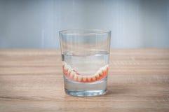 Nadada de los dientes falsos en vidrio de agua transparente Foto de archivo libre de regalías