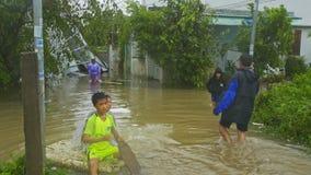 Nadada de los muchachos en tablón a lo largo de la calle inundada después del tifón