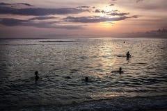 Nadada de los niños en la puesta del sol de la tarde del océano Imagen de archivo