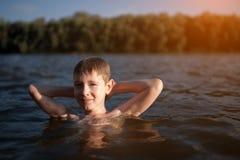 Nadada del niño pequeño en agua azul en la puesta del sol; Imagen de archivo