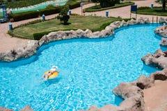 Nadada hermosa de la mujer joven en conservante de vida en piscina fotos de archivo