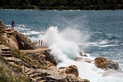 A nadada na pulverização acena na costa selvagem perto de Rovinj, Croati Imagens de Stock