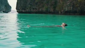 Nadadas de la muchacha en agua de la turquesa en la bahía almacen de video