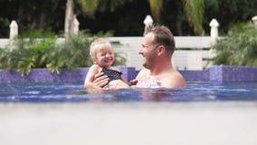 Nadadas del papá con su pequeña hija en la piscina almacen de metraje de vídeo