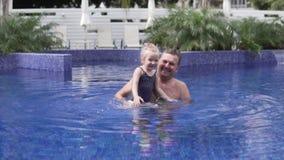 Nadadas del papá en la piscina con su pequeña hija almacen de video